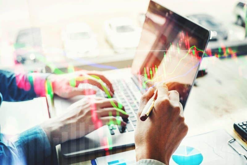 Dos hombres de negocios que trabajan en mercado de acción del ordenador portátil intercambian los inf imagen de archivo