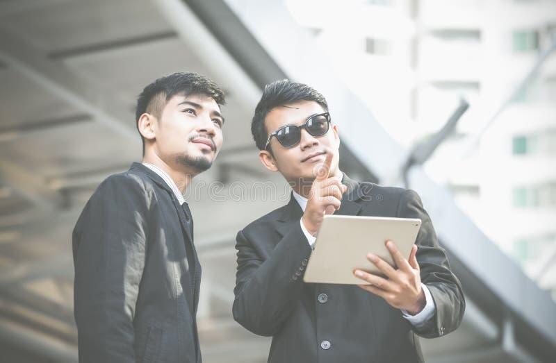 Dos hombres de negocios serios jovenes usando una tableta y un pointin digitales imágenes de archivo libres de regalías