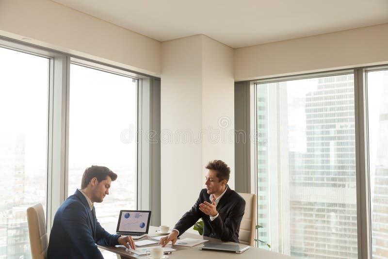 Dos hombres de negocios serios que discuten el proyecto, analizando ingenio del crecimiento imagen de archivo libre de regalías