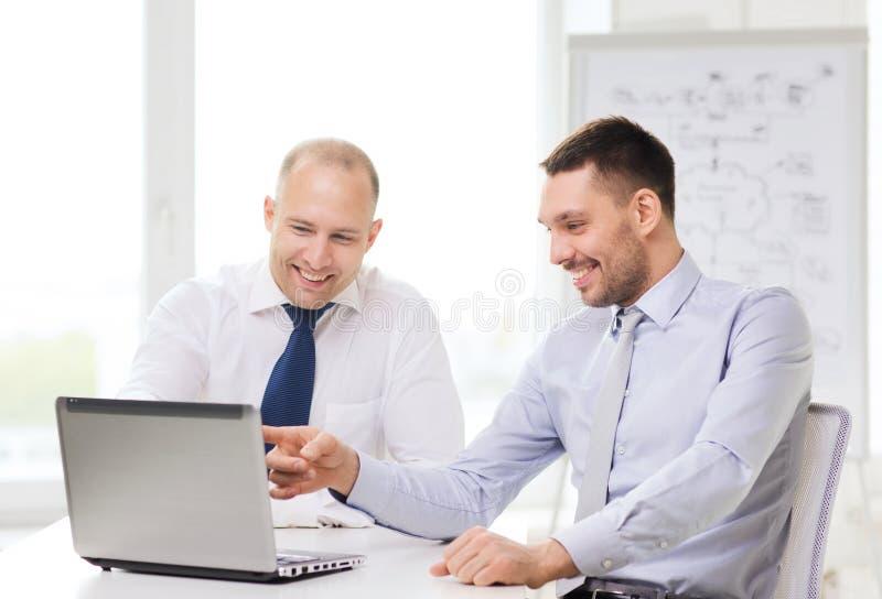Dos hombres de negocios sonrientes con el ordenador portátil en oficina foto de archivo
