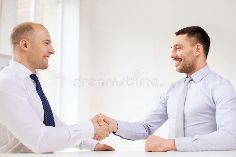 Dos hombres de negocios sonrientes que sacuden las manos en oficina imagen de archivo libre de regalías