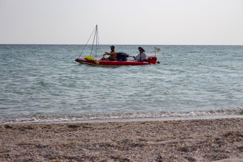 Dos hombres desconocidos en el barco de goma con los buques y navegación ucraniana de la bandera a lo largo de la costa Vacacione imagen de archivo