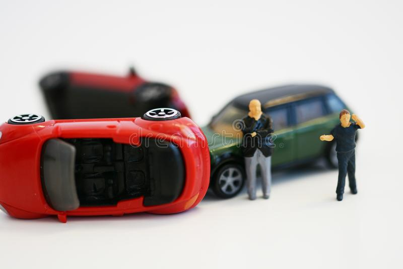 Dos hombres desesperados cerca de los coches del juguete implicados en accidente, imagen conceptual con las miniaturas y las esta fotografía de archivo libre de regalías