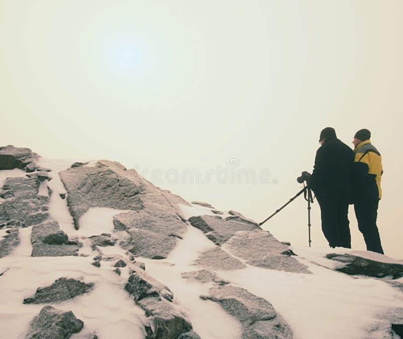 Dos hombres disfrutan del invierno photographying en montañas nevosas Fotógrafo de la naturaleza imagenes de archivo