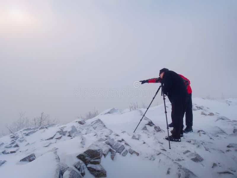 Dos hombres disfrutan del invierno photographying en montañas nevosas Fotógrafo de la naturaleza fotografía de archivo