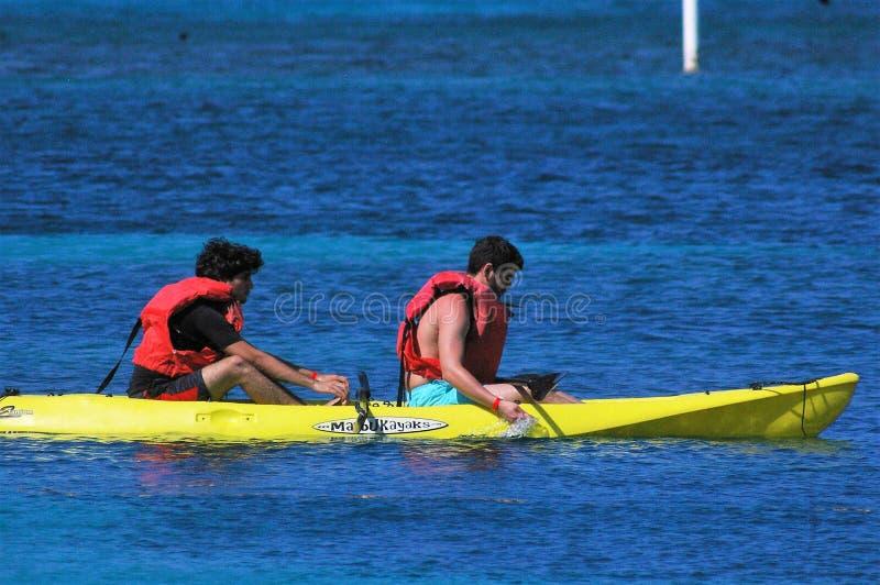 Dos hombres el las vacaciones que navegan una canoa amarilla fotografía de archivo libre de regalías