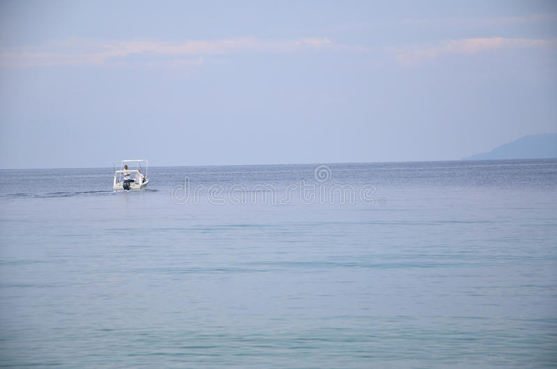 Dos hombres en barco en el mar imagen de archivo