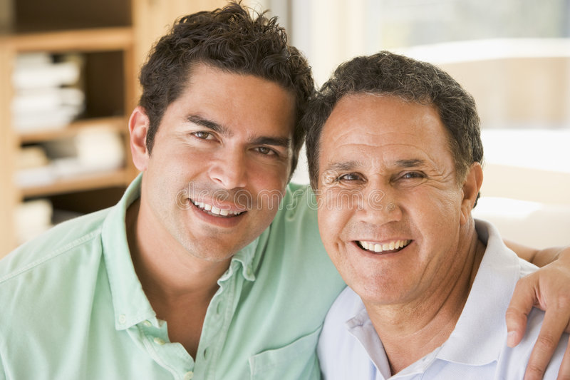 Dos hombres en la sonrisa de la sala de estar fotos de archivo