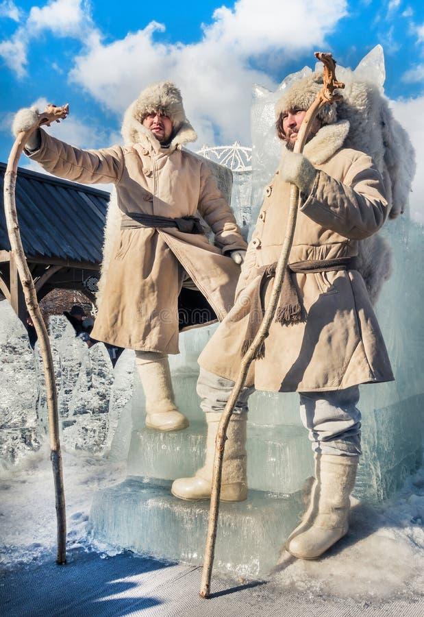 Dos hombres en los abrigos de pieles blancos que se colocan al lado del trono del hielo Adiós al invierno adentro fotos de archivo