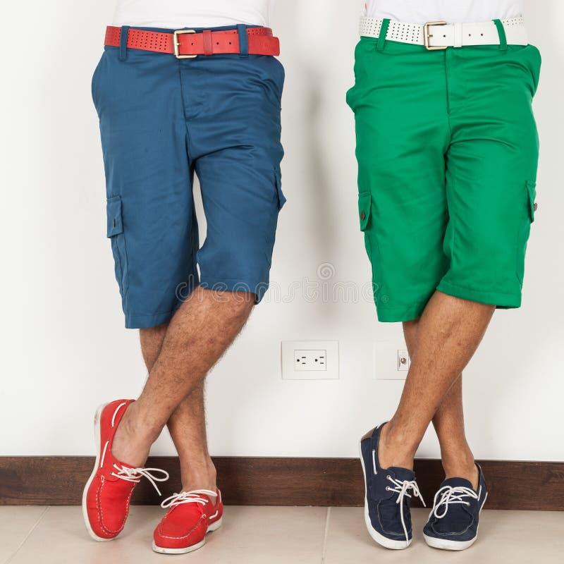 Dos hombres en los pantalones cortos verdes y los colores azules en el fondo blanco imagen de archivo