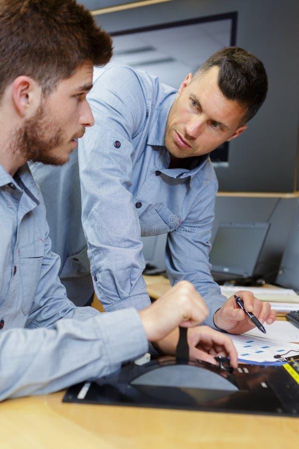 Dos hombres en oficina con la lista de control imagen de archivo