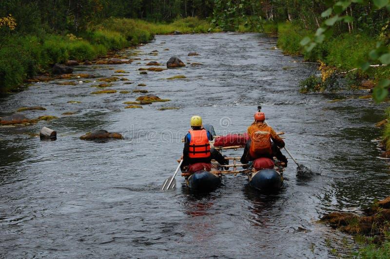 Dos hombres en un catamarán transportan en balsa rio abajo del taiga imagen de archivo libre de regalías
