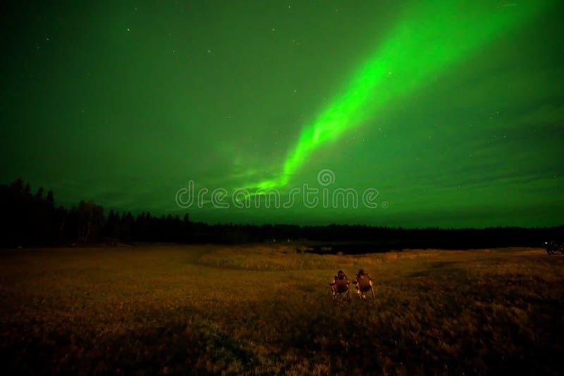 Dos hombres en una silla viendo Aurora borealis o las luces del norte en Yellowcuchillo, Canadá, en agosto, foto de archivo