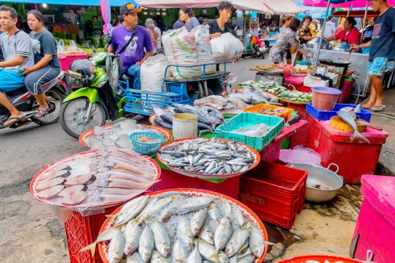 Dos hombres están entregando el hielo a la tienda de los pescados frescos en la calle con su vendedor que muestra forma de vida t imagen de archivo libre de regalías
