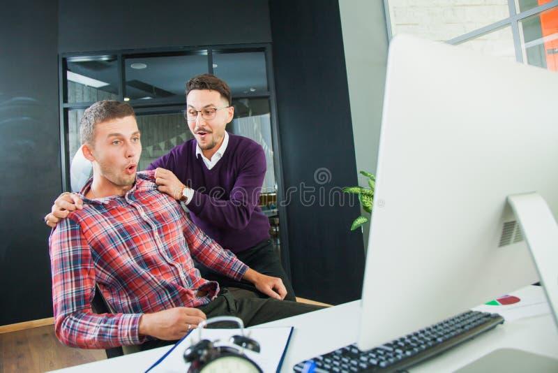 Dos hombres felices cerca del monitor de computadora, momento alegre imagen de archivo
