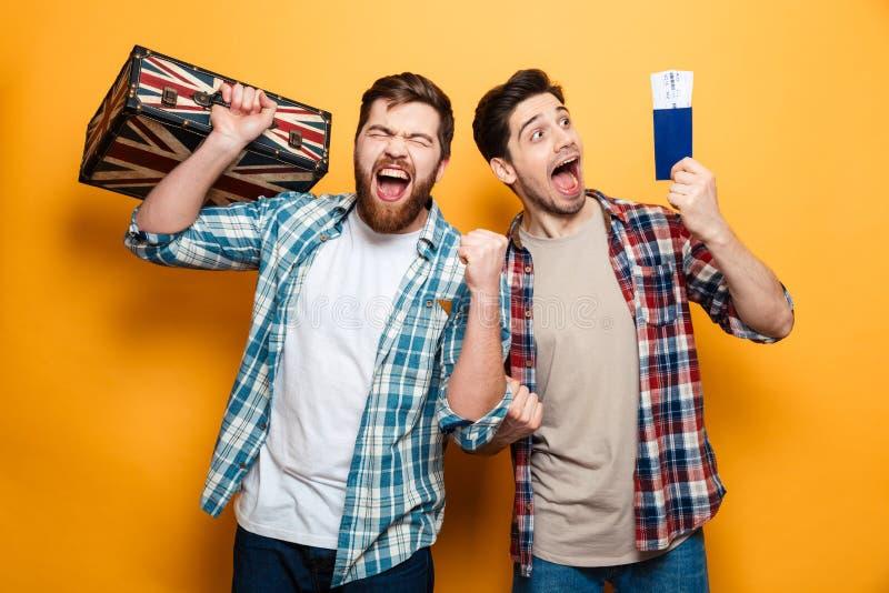 Dos hombres felices en las camisas que se colocan con la maleta y el pasaporte imagenes de archivo