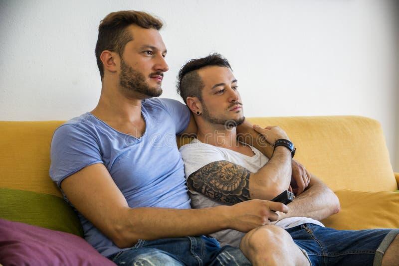 Dos hombres gay en el sofá que abrazan en casa fotografía de archivo