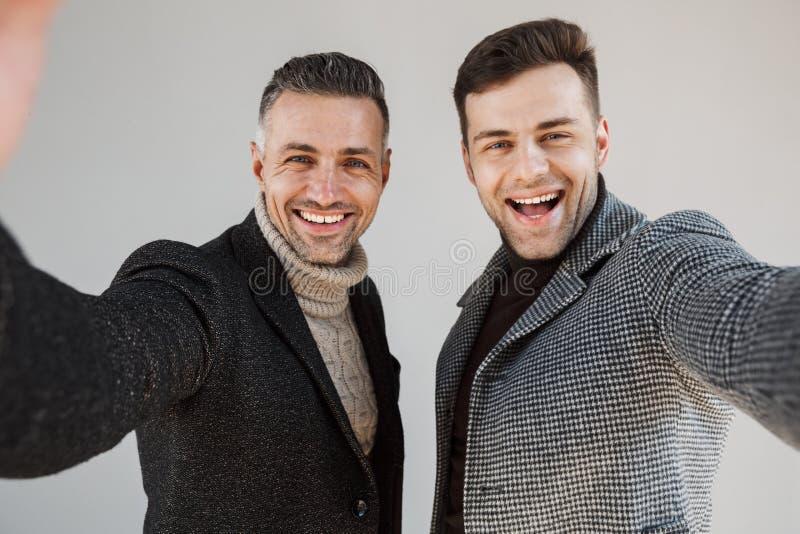 Dos hombres hermosos que llevan las capas sobre fondo gris fotos de archivo