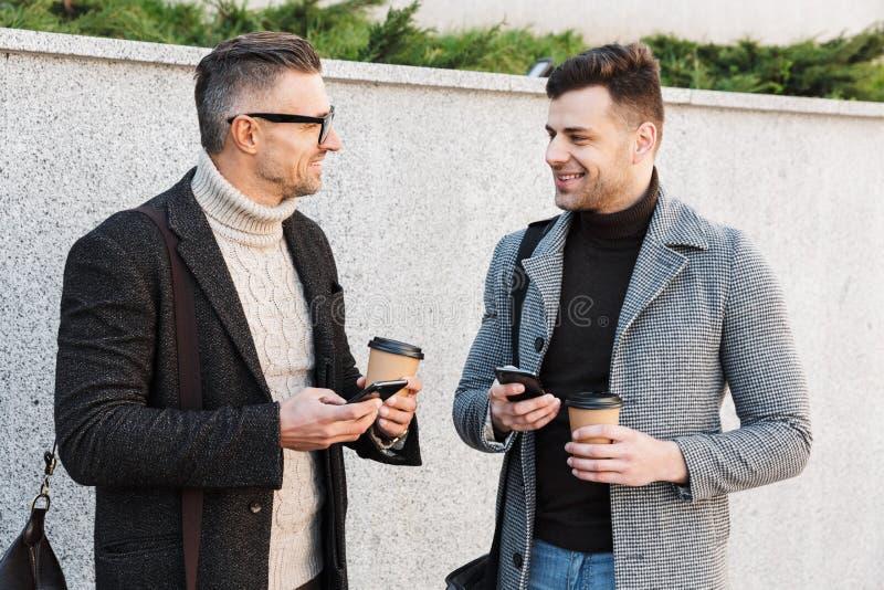 Dos hombres hermosos que llevan tiempo del gasto de las capas imágenes de archivo libres de regalías