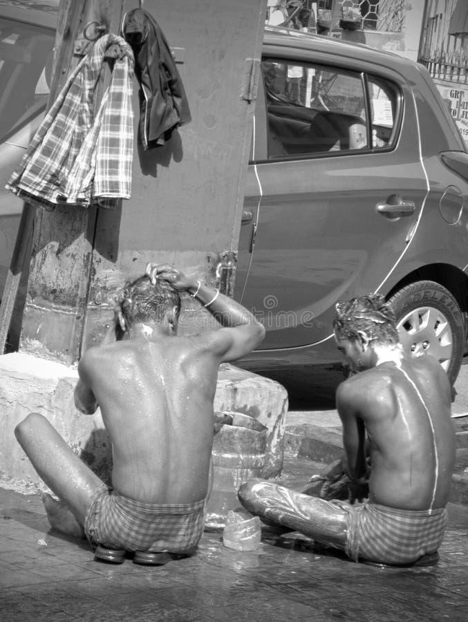 Dos hombres indios vistos de detrás ducha al lado de un coche parqueado en una calle de Kolkata, la India imágenes de archivo libres de regalías