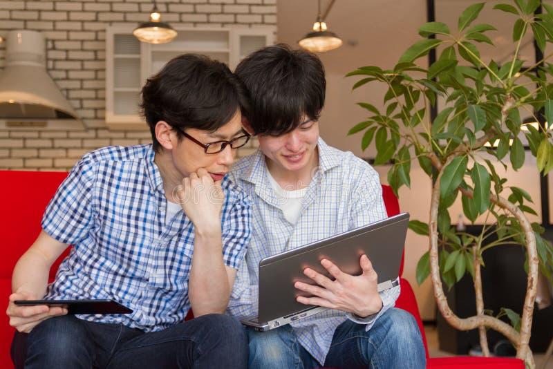 Dos hombres japoneses que miran contenido en Internet con el ordenador portátil fotos de archivo libres de regalías