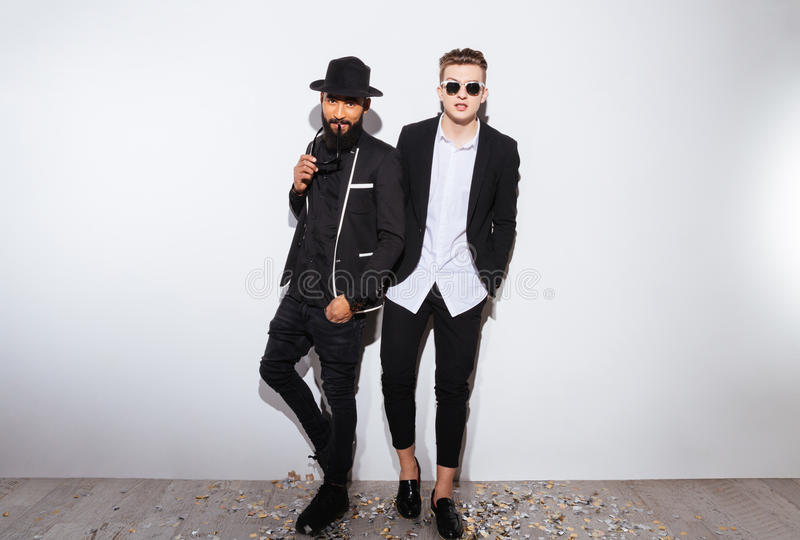 Dos hombres jovenes confiados atractivos en trajes negros modernos fotos de archivo libres de regalías