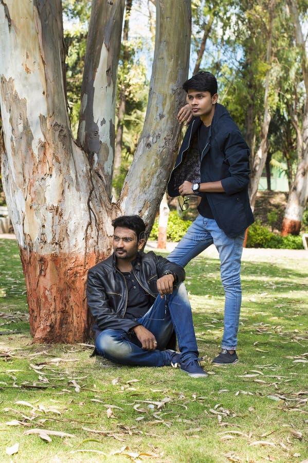 Dos hombres jovenes en ropa de moda casual en un parque fotografía de archivo