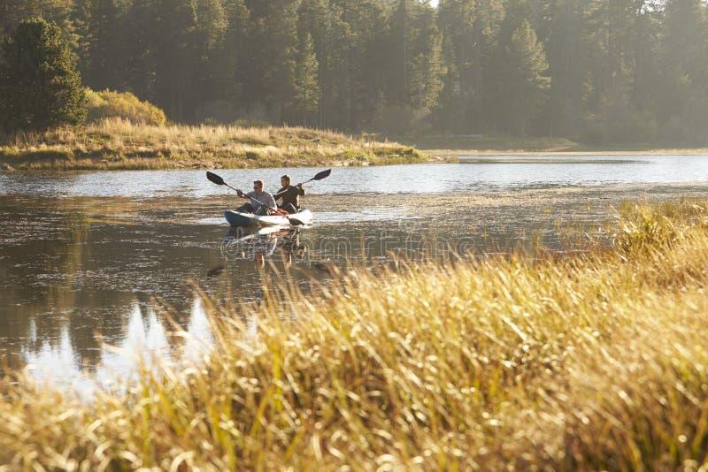 Dos hombres jovenes kayaking en un lago, hierba alta en primero plano imagenes de archivo