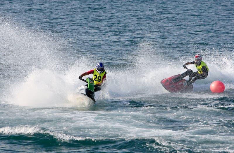 Dos hombres jovenes que apresuran adelante en jetbike durante una raza imagenes de archivo