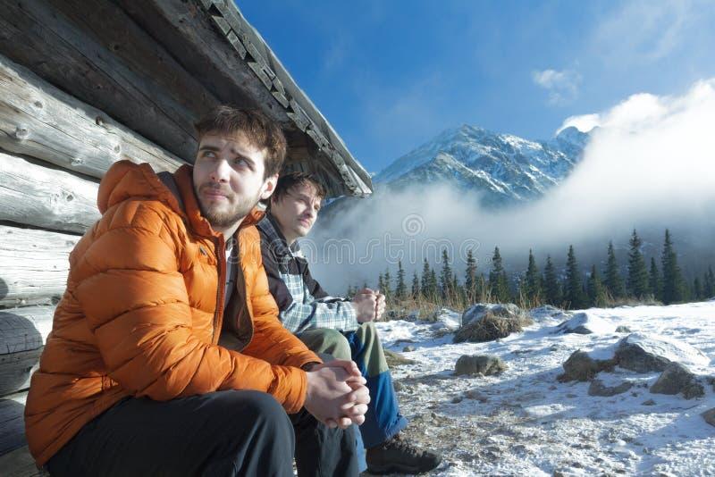 Dos hombres jovenes que descansan sobre banco de madera en montañas del invierno al aire libre fotos de archivo