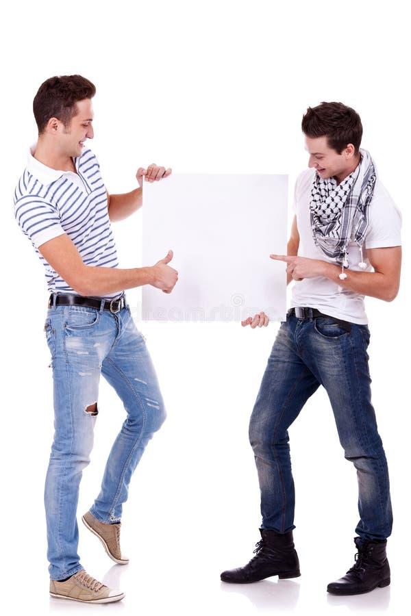 Dos hombres jovenes que llevan a cabo a una tarjeta en blanco fotografía de archivo libre de regalías