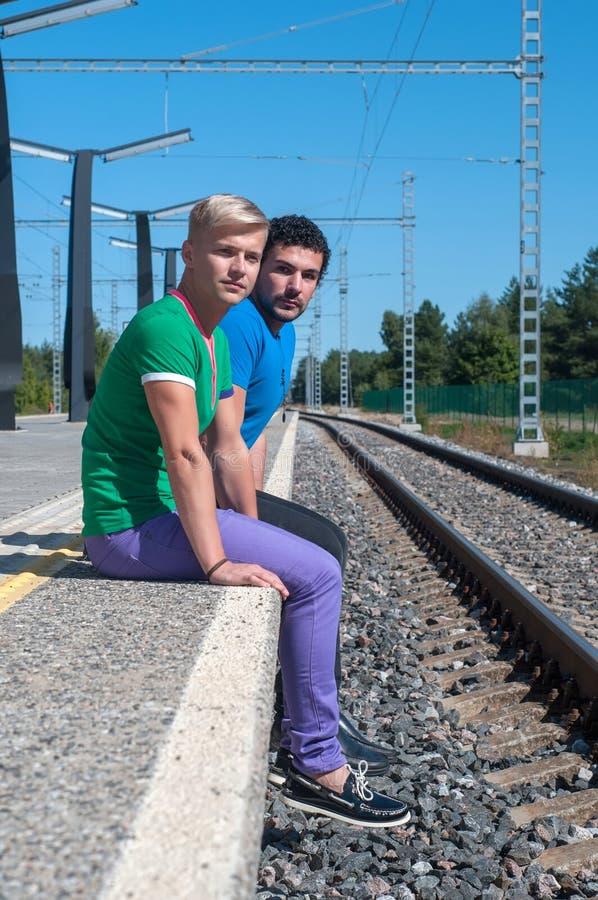 Dos hombres jovenes que se sientan en la plataforma imagenes de archivo
