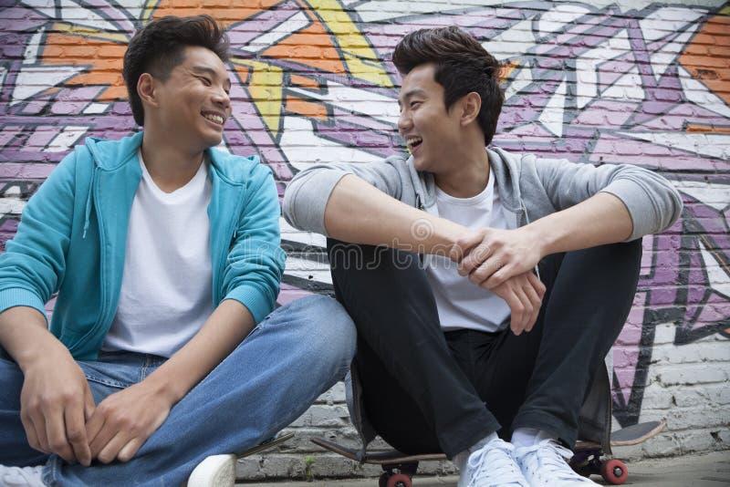 Dos hombres jovenes que se sientan en sus monopatines y que cuelgan hacia fuera delante de una pared con la pintada imagen de archivo