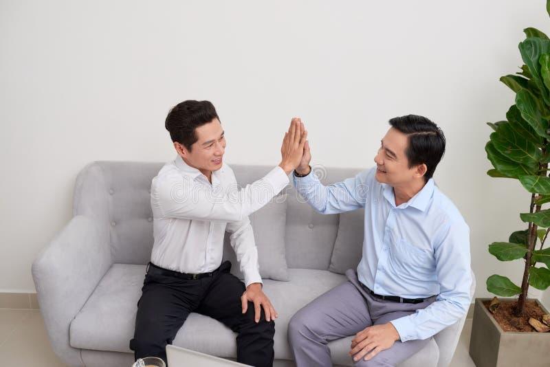 Dos hombres jovenes que trabajan con el ordenador port?til y la tableta que se sientan en el sof? imagenes de archivo