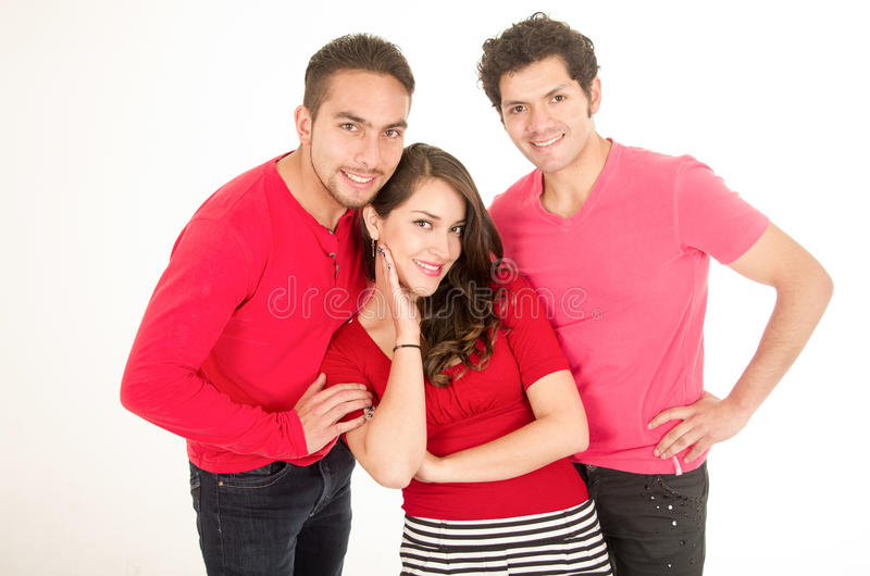 Dos hombres jovenes y una chica joven se vistieron en rojo fotografía de archivo