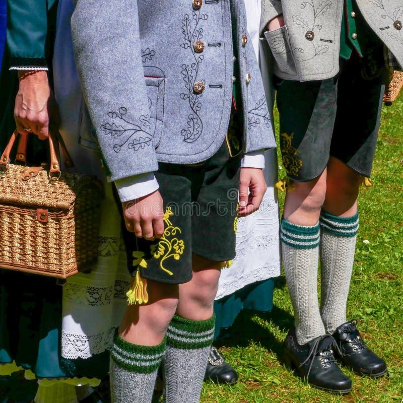 Dos hombres jovenes y una mujer que lleva la ropa bávara tradicional alemana, colocándose en un día soleado ningunas caras fotos de archivo