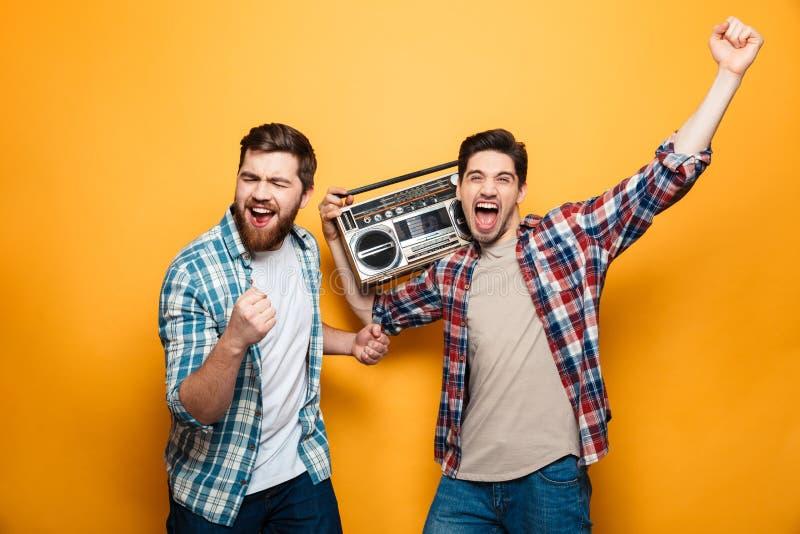 Dos hombres juguetones en música que escucha de las camisas del tocadiscos imagen de archivo libre de regalías