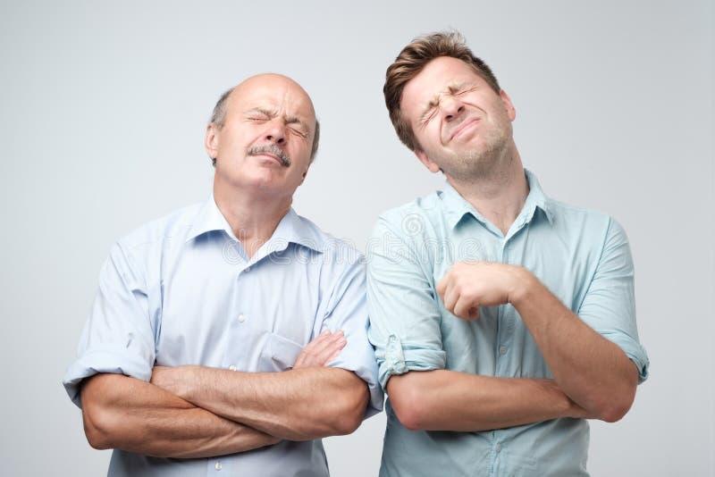 Dos hombres maduros padre e hijo con agujereado alimentado encima de la expresión, miradas descontentaron para arriba fotos de archivo libres de regalías