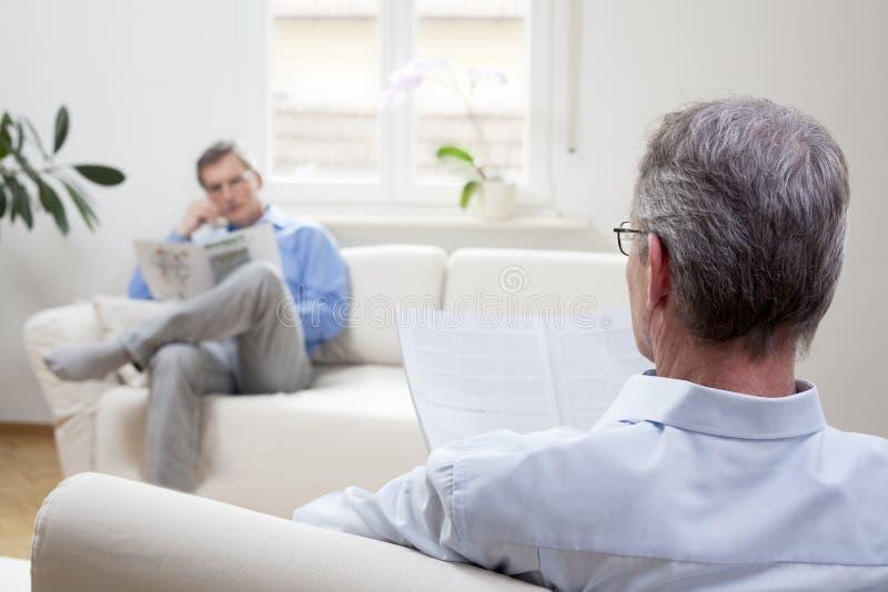 Dos hombres maduros sentados en un salón y leyendo un periódico foto de archivo libre de regalías