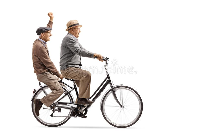 Dos hombres mayores alegres que montan una bicicleta junto imagenes de archivo
