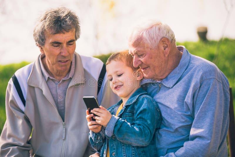 Dos hombres mayores y nieto que usa el teléfono elegante fotos de archivo libres de regalías