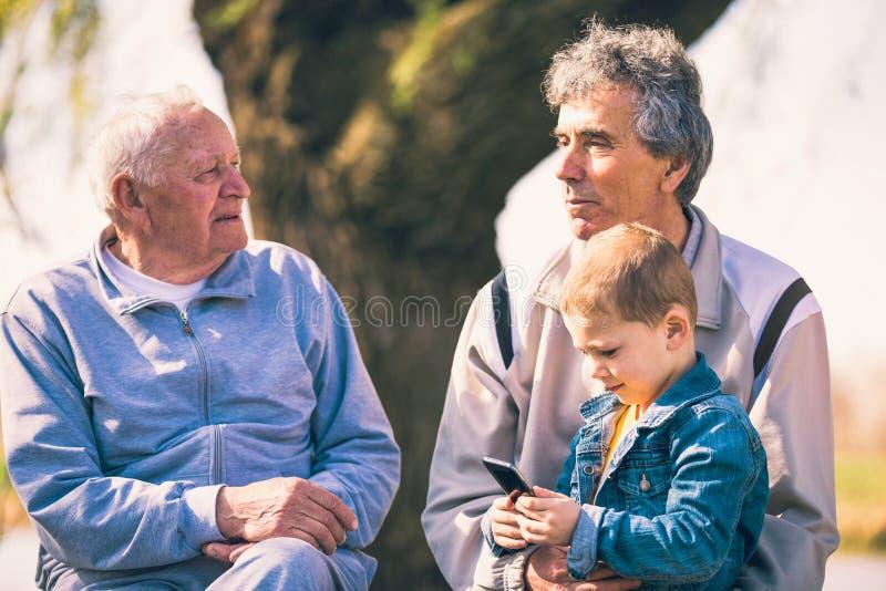Dos hombres mayores y nieto que usa el teléfono elegante foto de archivo