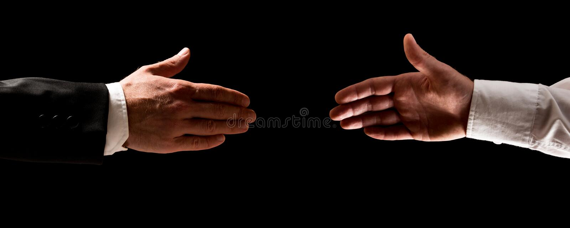 Dos hombres que alcanzan hacia fuera para sacudir las manos fotos de archivo