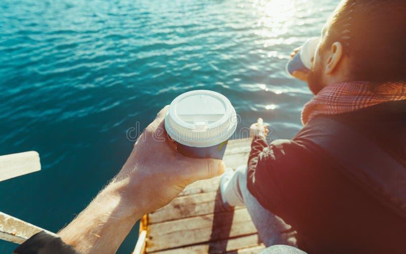 Dos hombres que beben el café que se sienta en el embarcadero y que disfruta de la opinión del mar, tiro de Point of View foto de archivo