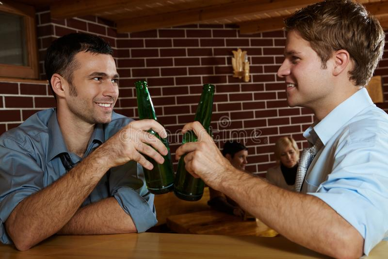 Dos hombres que beben la cerveza en barra fotografía de archivo libre de regalías