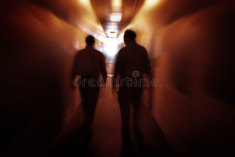Dos hombres que caminan a través del túnel que explora nuevos lugares foto de archivo libre de regalías