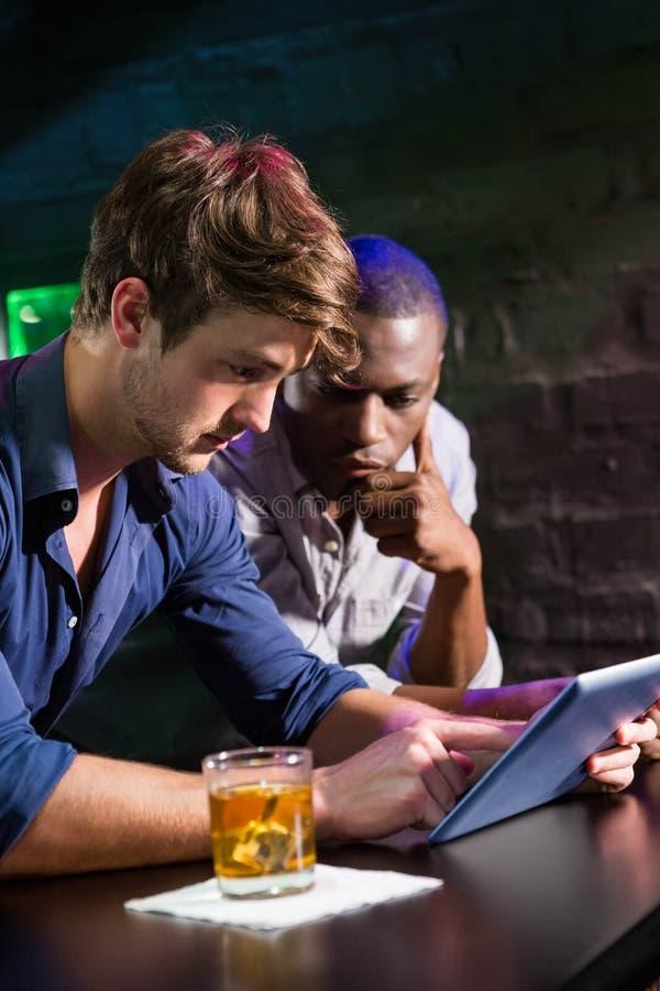 Dos hombres que comen whisky y que usan la tableta digital en el contador de la barra fotos de archivo
