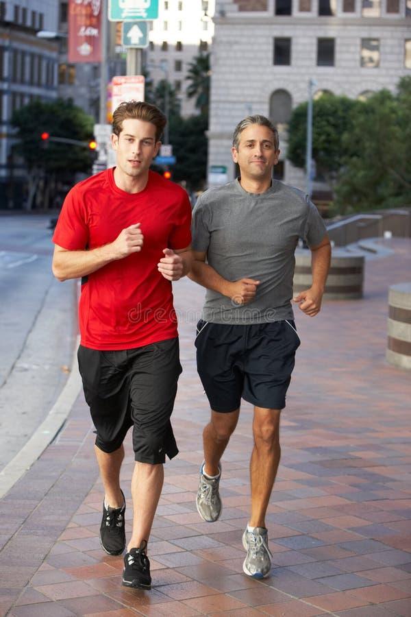 Dos hombres que corren en la calle urbana imágenes de archivo libres de regalías