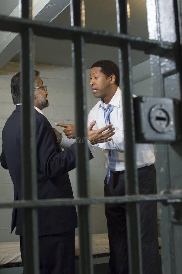 Dos hombres que discuten en celda de prisión foto de archivo libre de regalías