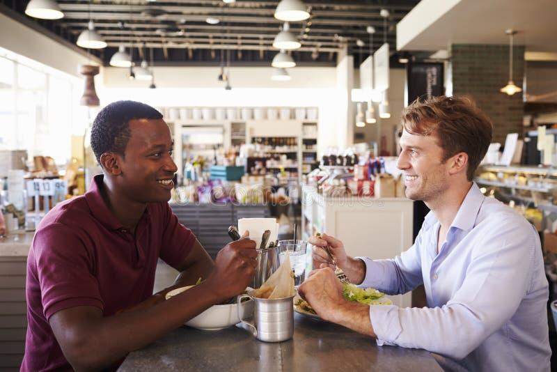 Dos hombres que disfrutan del almuerzo en restaurante de la charcutería fotos de archivo